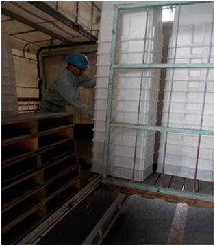 トラックに空の角ポリ容器を積み込む作業